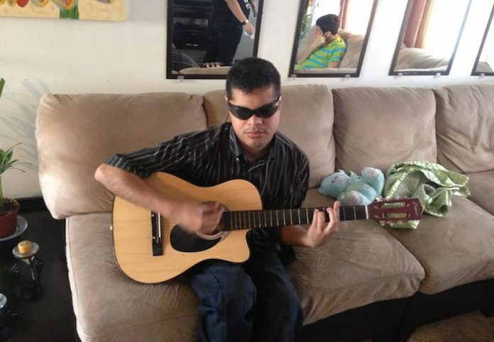Blind Musician Edgar Cabachuela Of Many Talents Playing One of Many Instruments and Singer