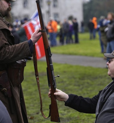 image of two men passing each other guns, unintentionally phallic looking