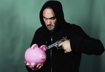 man pointing gun at piggy bank