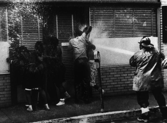 image of civil rights protesters being sprayed by a hose
