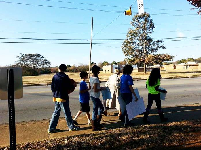 Forced-birth commandos lead children in a protest across the street from a school